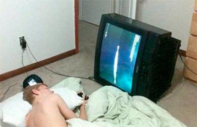 смотрит лежа телевизор